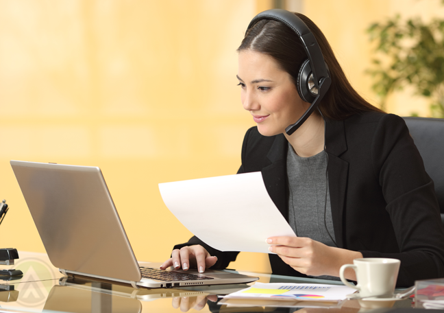 smiling-customer-service-call-center-agent-using-laptop-holding-printed-document