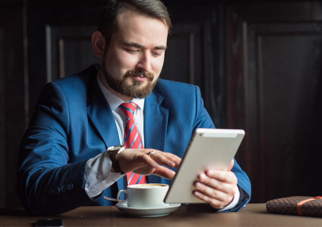 bearded-businessman-looking-reading-tablet-having-coffee