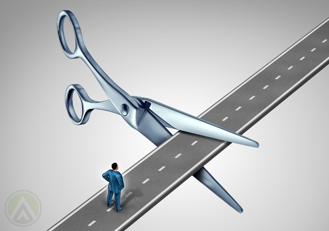 businessman-in-road-barred-by-giant-scissors