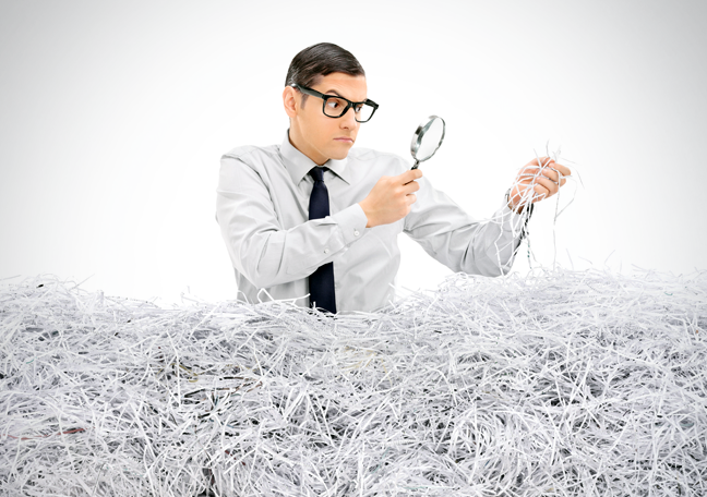 dorky-business-employee-by-piles-of-shredded-paper-looking-through-magnifying-lens