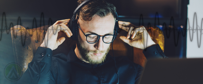 bearded-businessman-in-glasses-listening-to-headphones