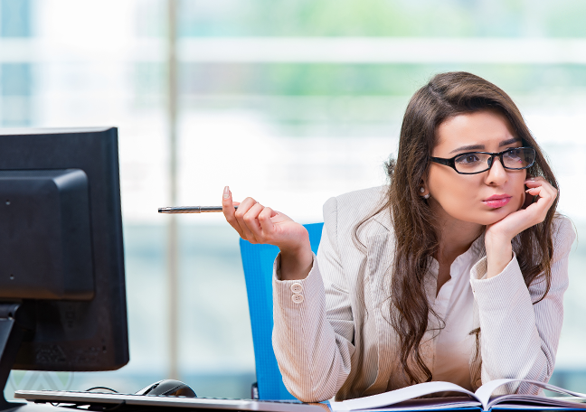 confused-office-worker-pointing-to-computer-monitor-with-pen