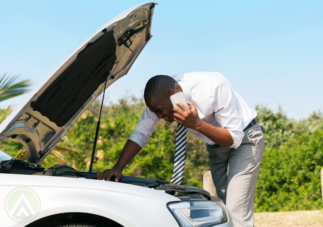 man on phone call looking at car trouble