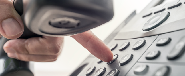 hand holding landline phone receiver while dialing