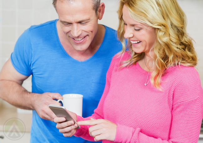 smiling-couple-in-bright-colored-clothes-looking-at-smartphone