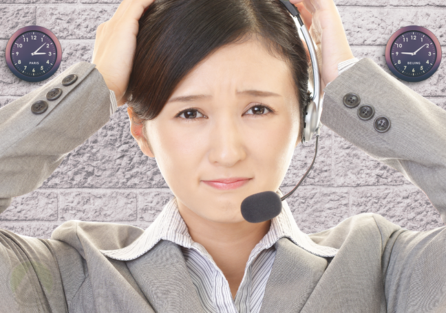 stressed asian call center agent with wall clocks in background