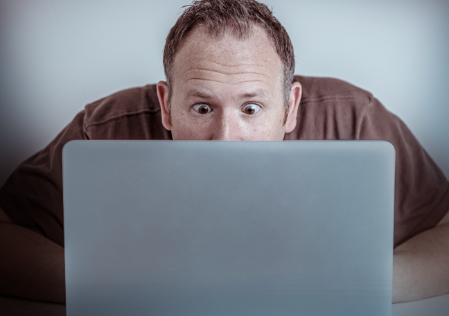 surprised man looking at laptop