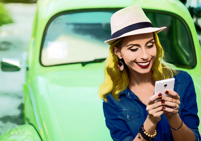 woman in blue using smartphone by car outdoors