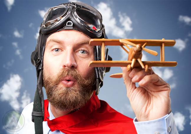 bearded man playing with toy plane blue sky backdrop