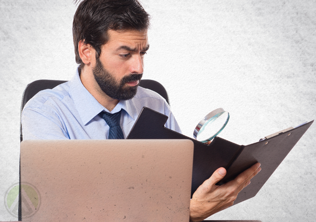 bearded office worker looking at folder of reports with magnifying lens