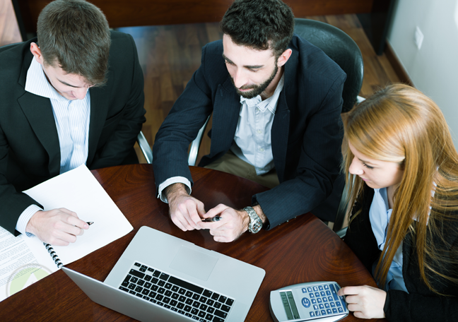 business team in meeting looking at laptop
