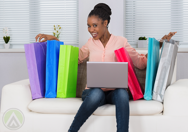 delighted woman excited sitting couch with shopping bags