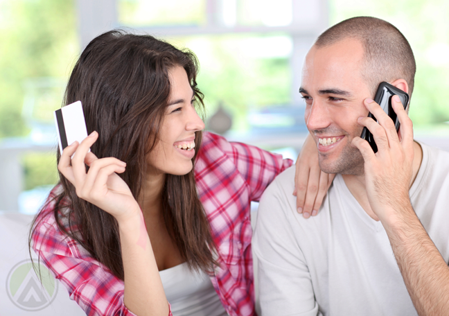 happy couple holding credit card while phone call