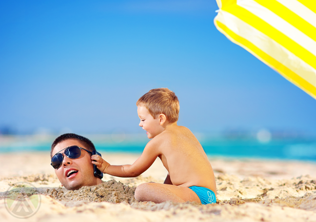 man in sunglasses partially burried in beach sand with toddler son holding phone