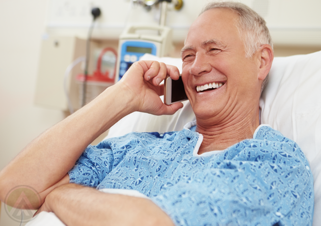 matured man making phone call in hospital bed