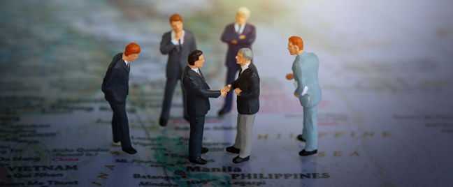 miniature businessmen shaking hands over Manila Philippines on World Map