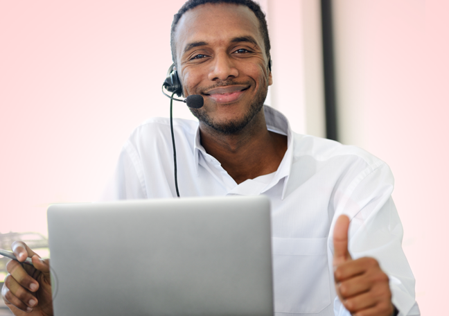smiling call center agent by laptop thumbs up