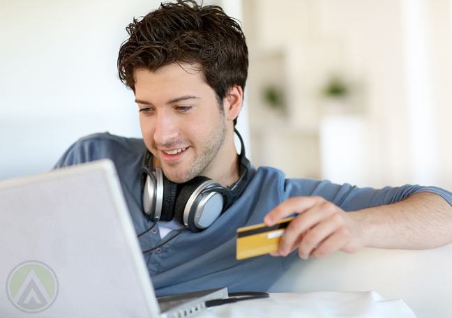 smiling man with headphones holding credit card doing online shopping