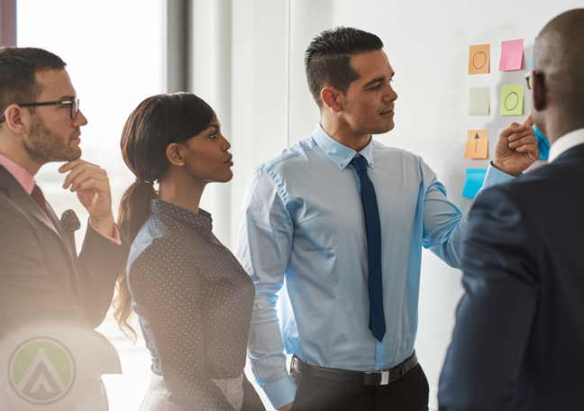 standing business executives in meeting pointing to post it
