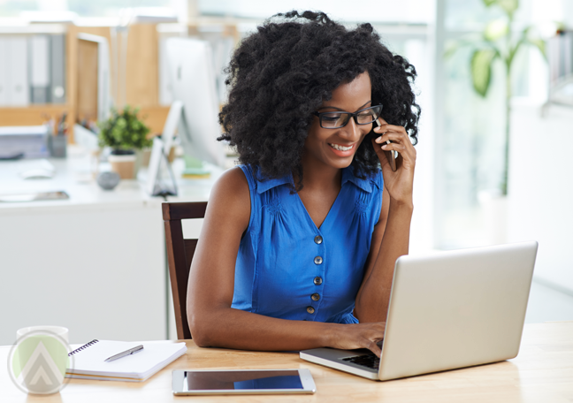 woman in blue using smartphone laptop tablet in office