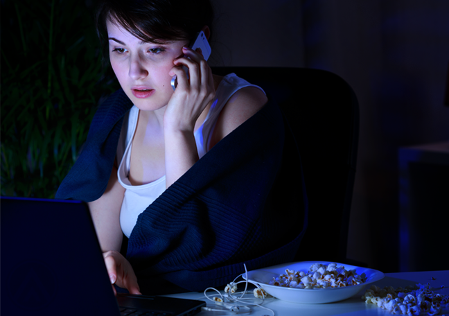 woman in phone call using laptop in dark room