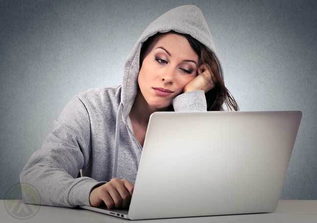 bored woman in hoodie using laptop