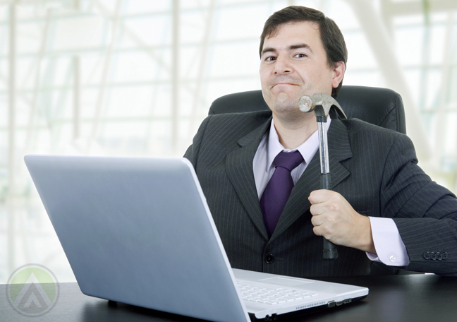 businessman holding hammer about to hit laptop