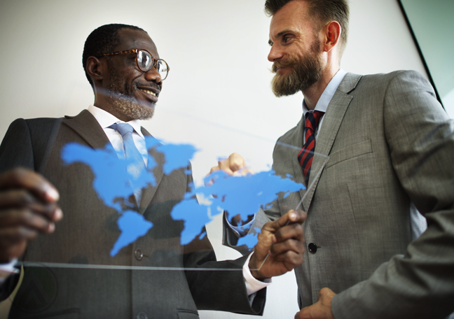 businessman looking at world map on clear glass
