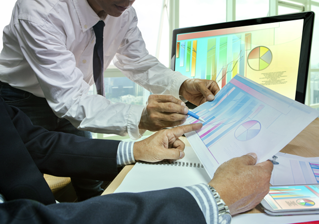 businessmen studying printed business report charts graphs