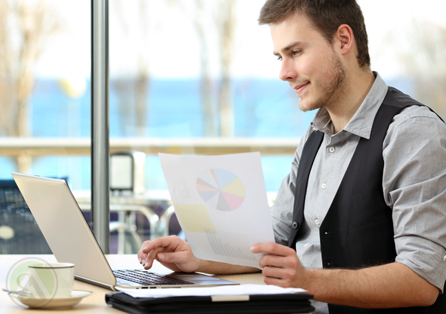 employee working on laptop with printed document
