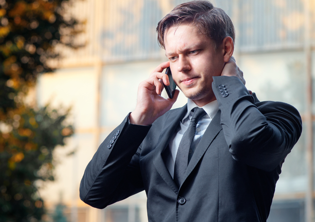 problematic businessman in phone call standing along outdoors