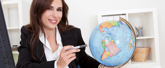 smiling businesswoman in office pointing pen at globe