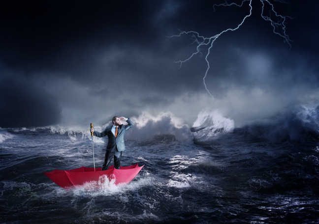business executive sailing in stormy waters on red umbrella