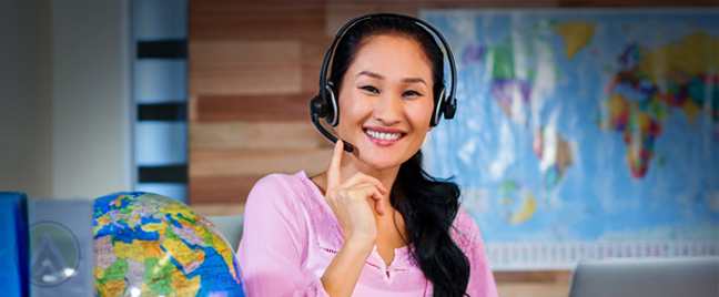 smiling asian travel support call center agent in office with map globe