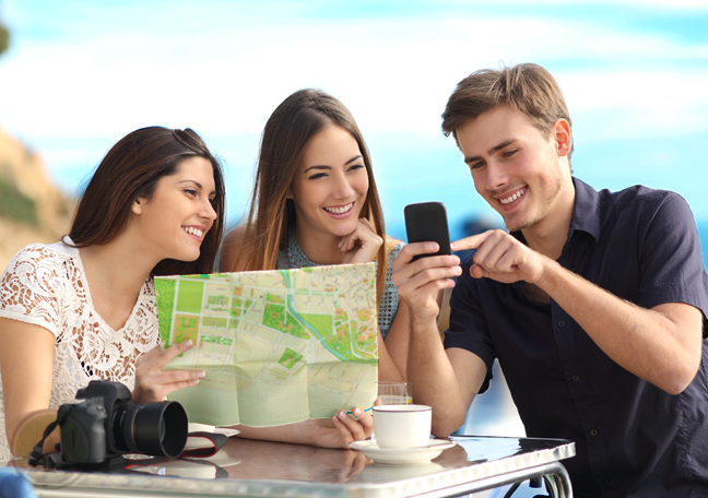 tourist group sitting outdoors looking at map smartphone