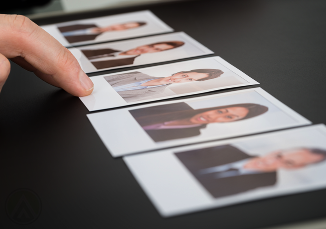 hand pointing to one photo group of executive pictures