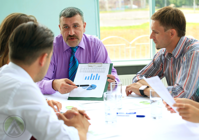 middle aged boss presenting chart to younger team