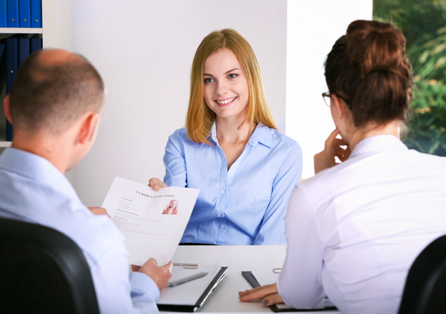young woman in job interview handing over resume to hr personnel