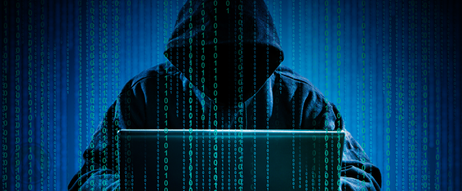 cloaked hacker working on cmputer