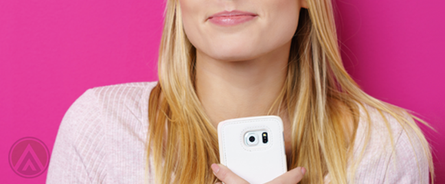 smiling blond woman hugging smartphone