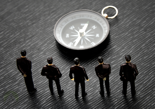 tiny human figures standing before compass