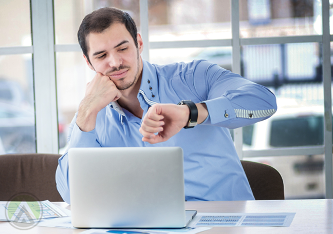 businessman using laptop impatiently looking at watch