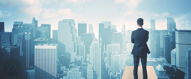 businessman on building rooftop looking over city buildings
