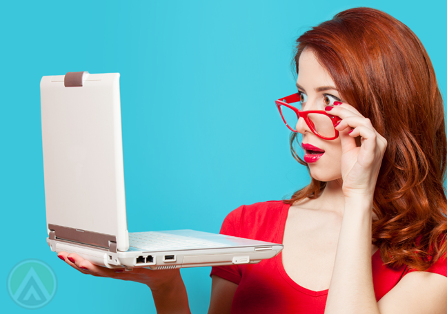 young woman in red dress glasses surprised look at laptop