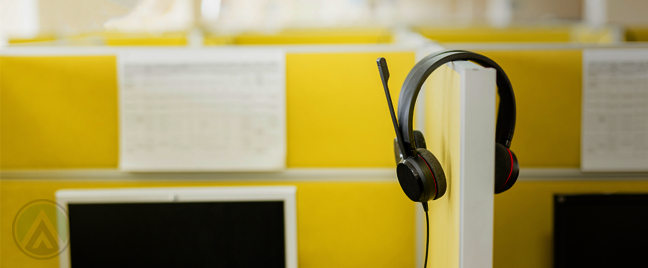 headset on yellow office divider in empty call center