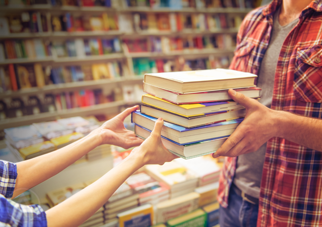 man handing piles of books to teenager