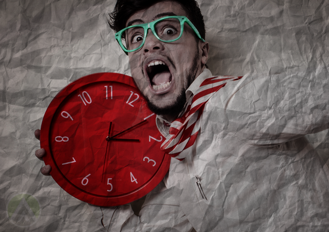 young customer support representative in call center panicking holding red wall clock
