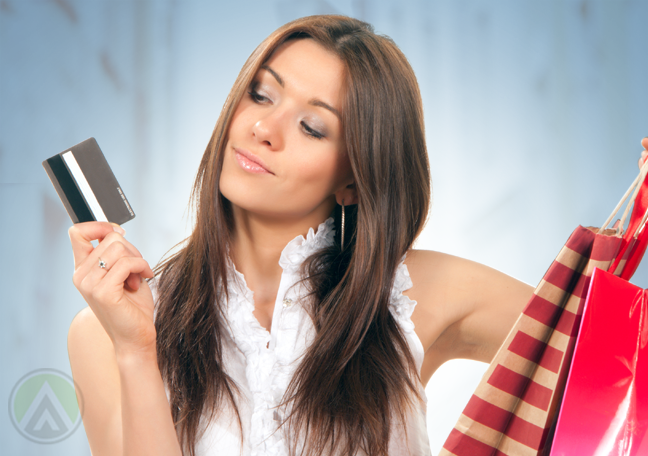 woman carrying shopping bags looking closely at credit card