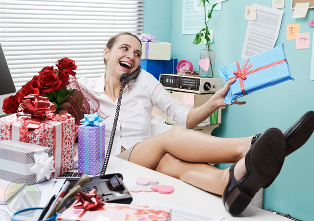 woman relaxing in office feet up surrounded by large gifts