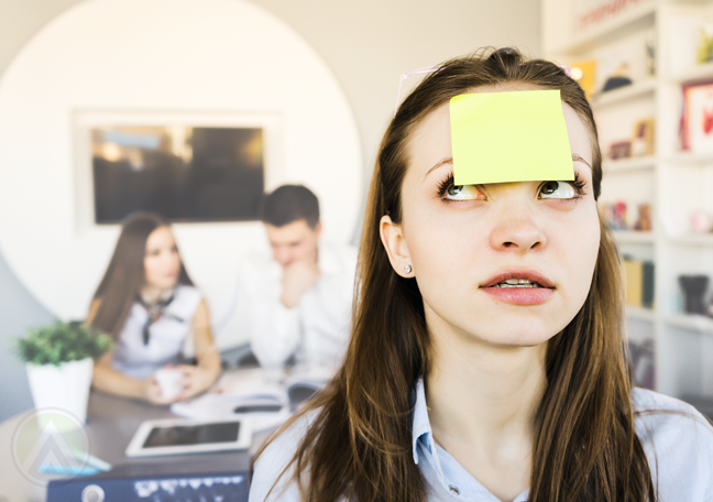 confused office employee with post it on forehead coworkers in back